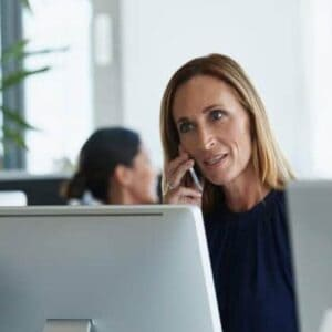 Businesswoman speaking on mobile phone at desk