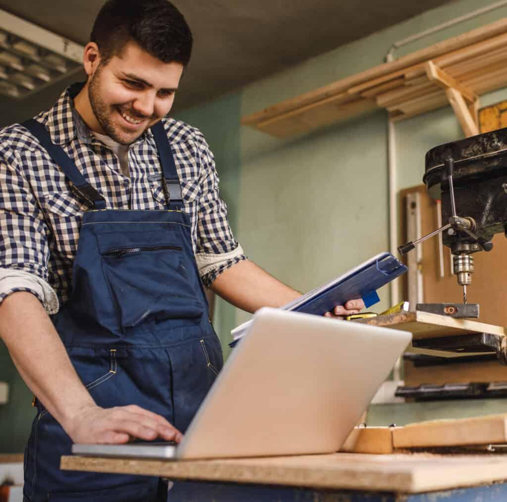 Smiling young carpenter using laptop