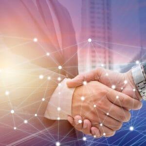 Businessmen shaking hands with digital pattern in background