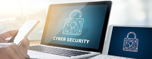 Hands holding mobile and looking at cybersecurity symbol on laptop screen